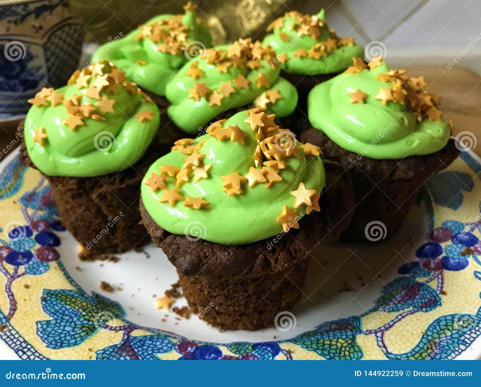 Les petits gâteaux avec se givrer vert et étoiles d or arrose d un plat blanc