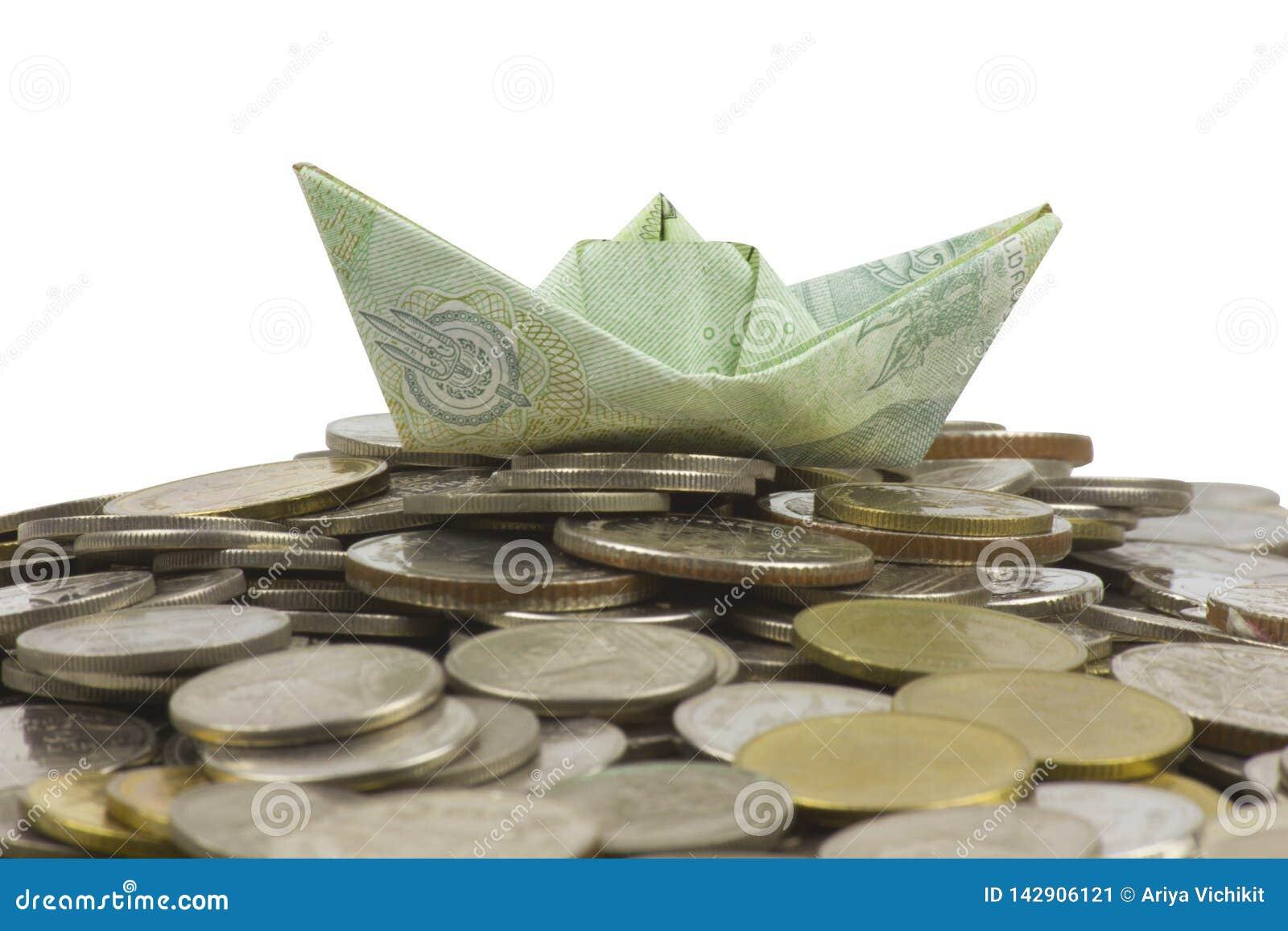 Les pièces et le billet de devise de la Thaïlande ont plié à l origami le voilier sur le fond blanc avec le chemin cipping