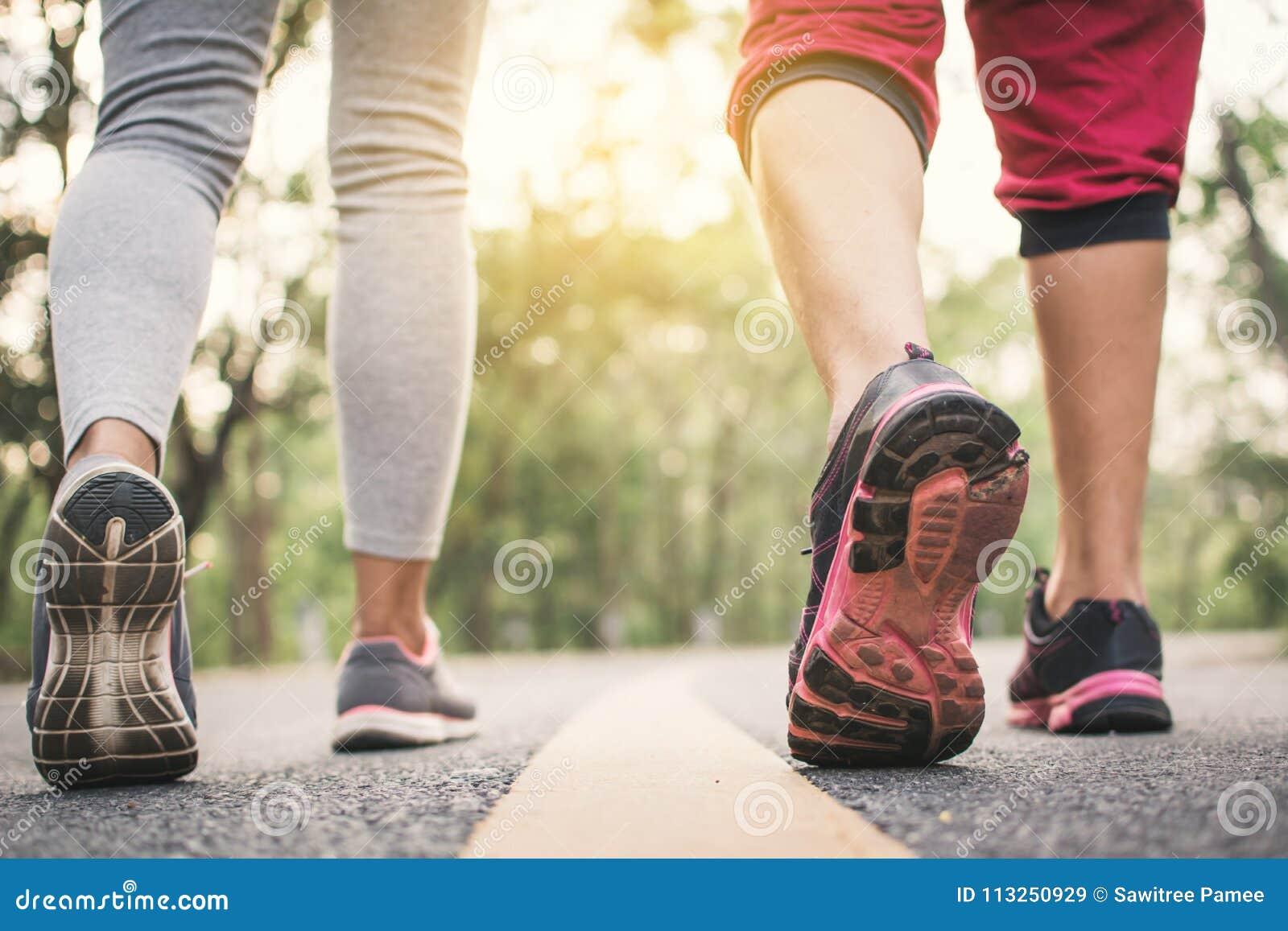 Les pieds équipent et femme courant sur la route pour la santé