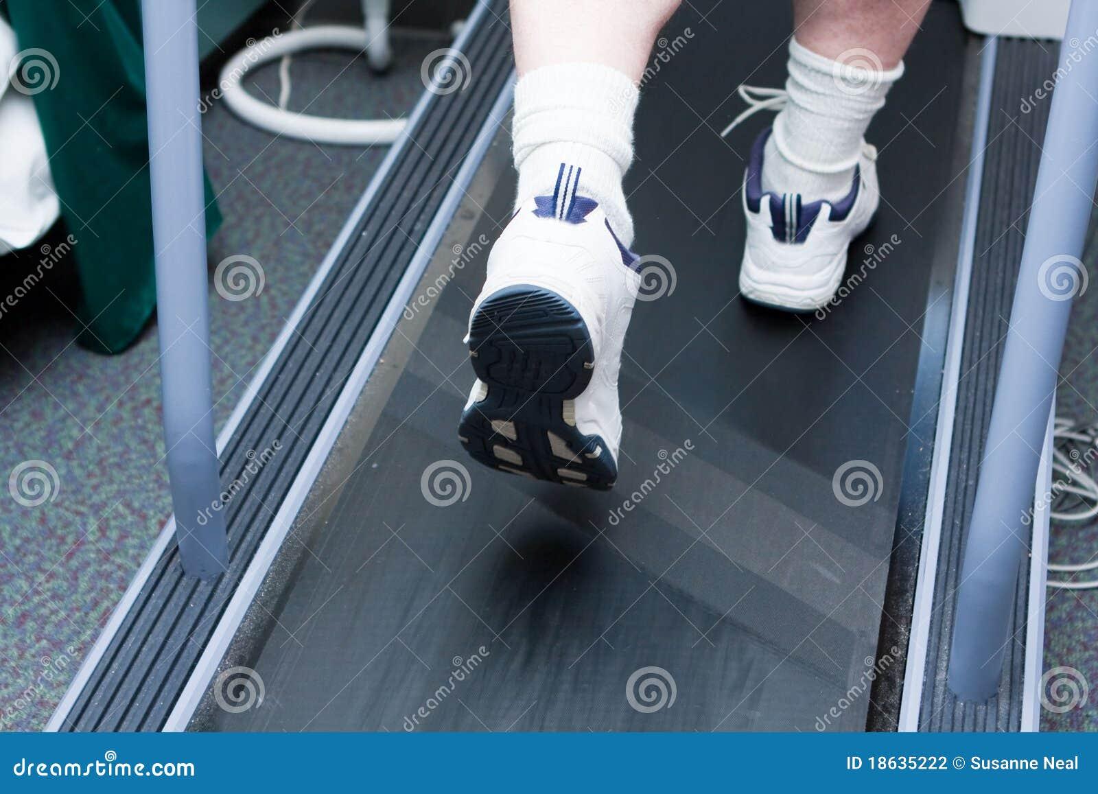 Les pieds de l homme fonctionnant sur le tapis roulant