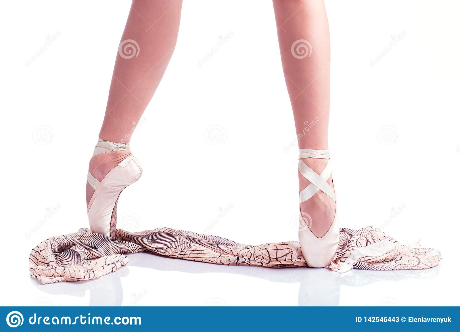Les pieds de la ballerine dans le pointe et avec l écharpe en soie sur le fond blanc