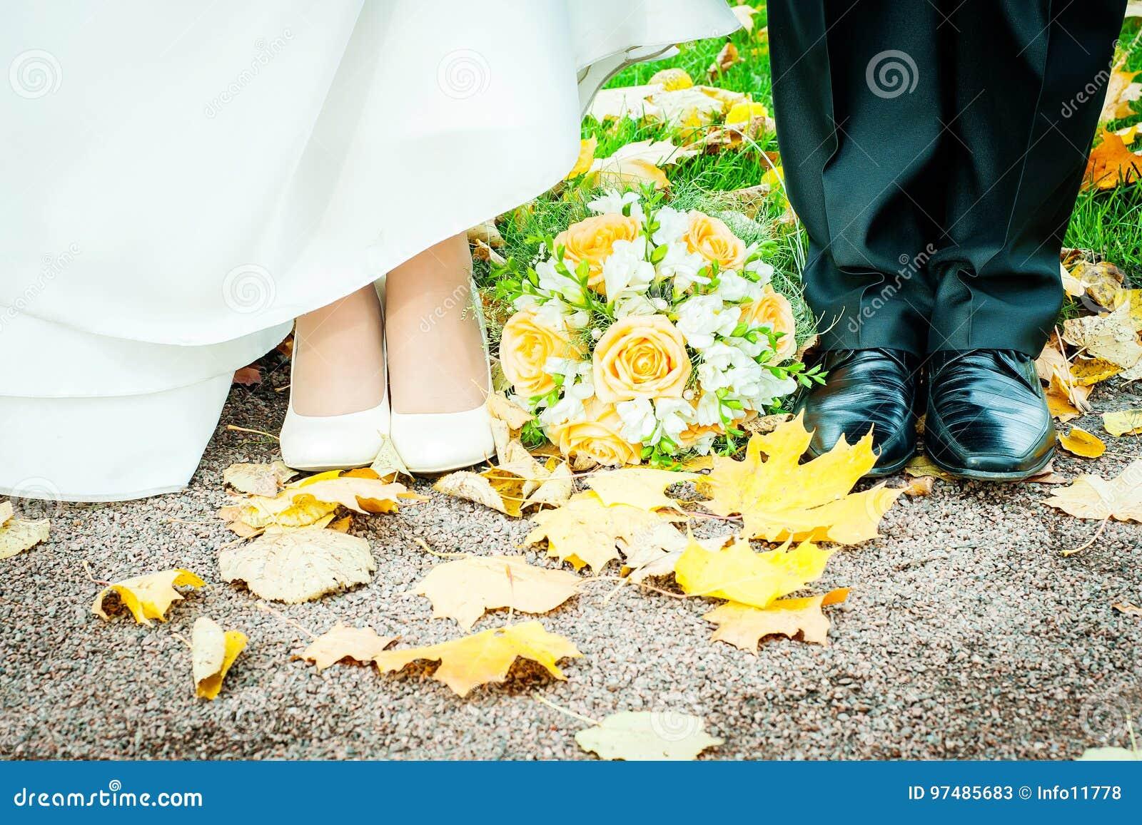 Les pieds des jeunes mariés en automne se garent