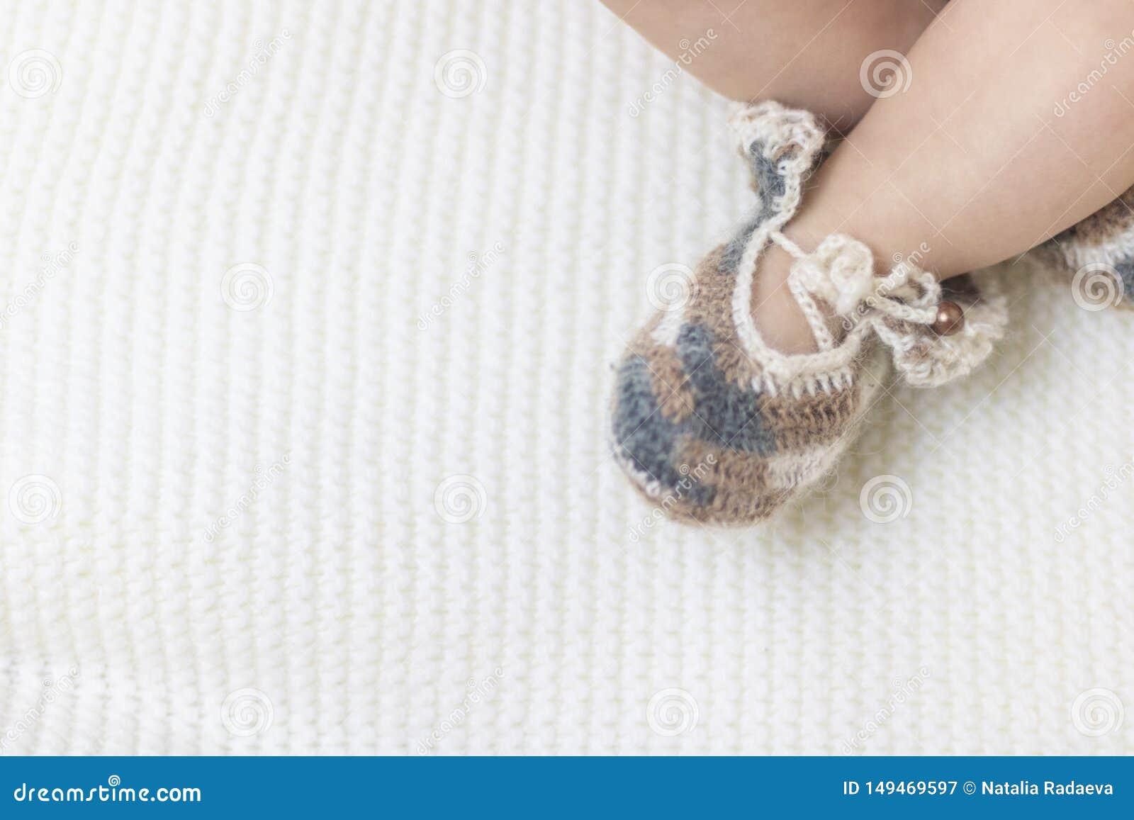 Les pieds nouveau-n?s de b?b? se ferment dans des butins tricot?s bruns de chaussettes de laine sur une couverture blanche Le b?b
