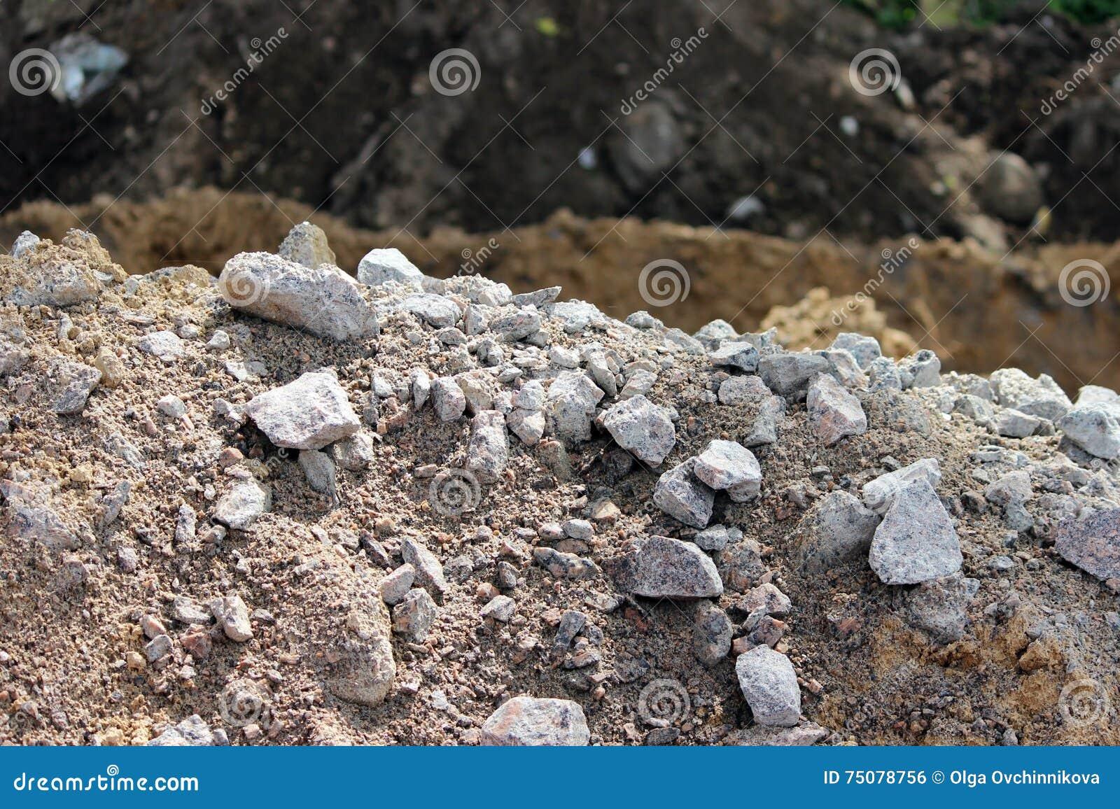 Les pierres de granit, sable et terre, ont creusé pendant l extraction de la préparation sur place de tourbe pour la construction