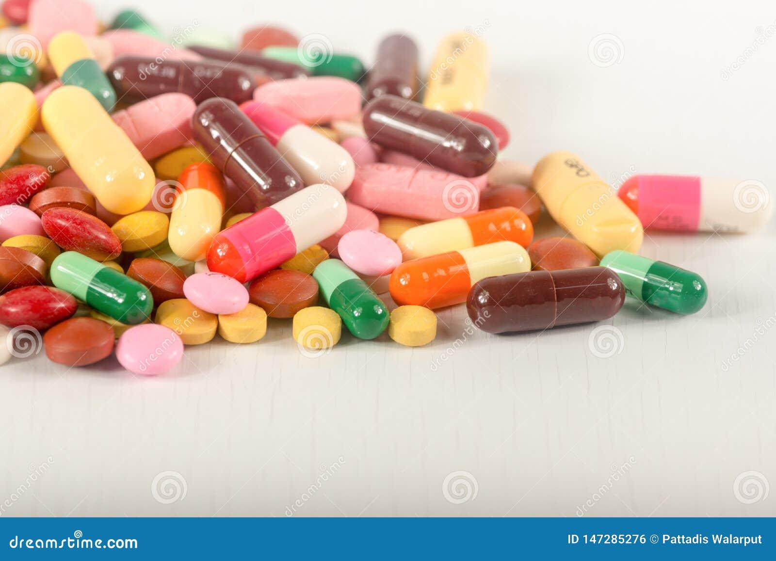 Les pilules colorées éclaboussent sur le fond blanc Les différents comprimés et drogues de thérapie de mélange de tas de capsule