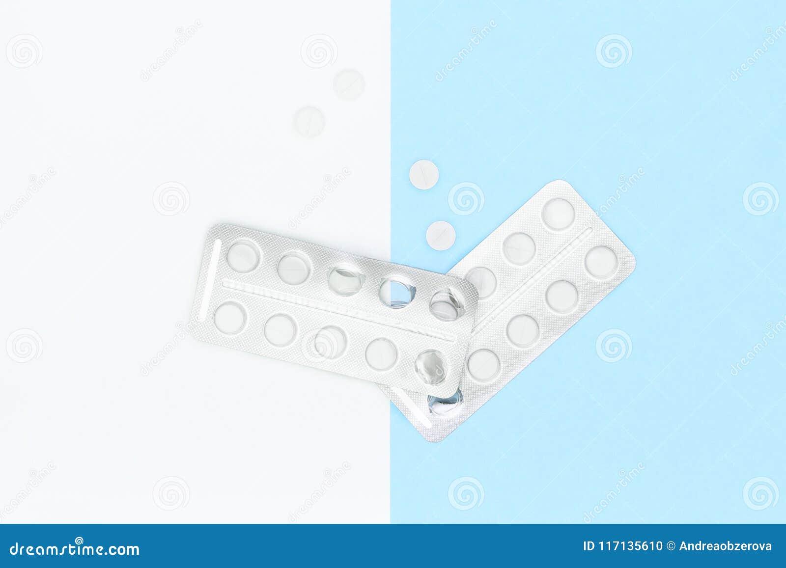 Les pilules et le habillage transparent blancs sur le pastel bleu ont coloré le fond Industrie pharmaceutique Épidémie et toxicom