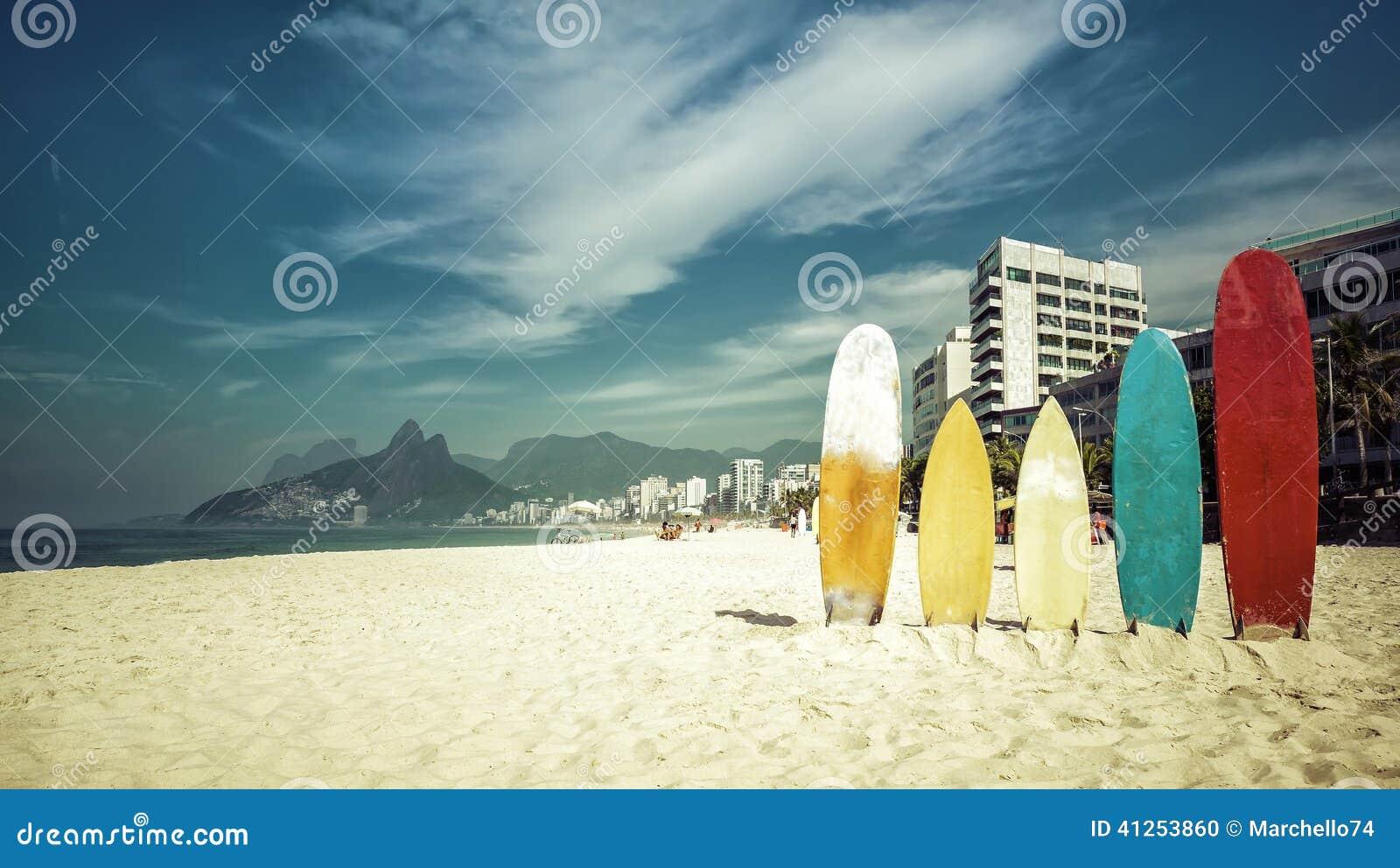 Les planches de surf se tenant en soleil lumineux sur Ipanema échouent