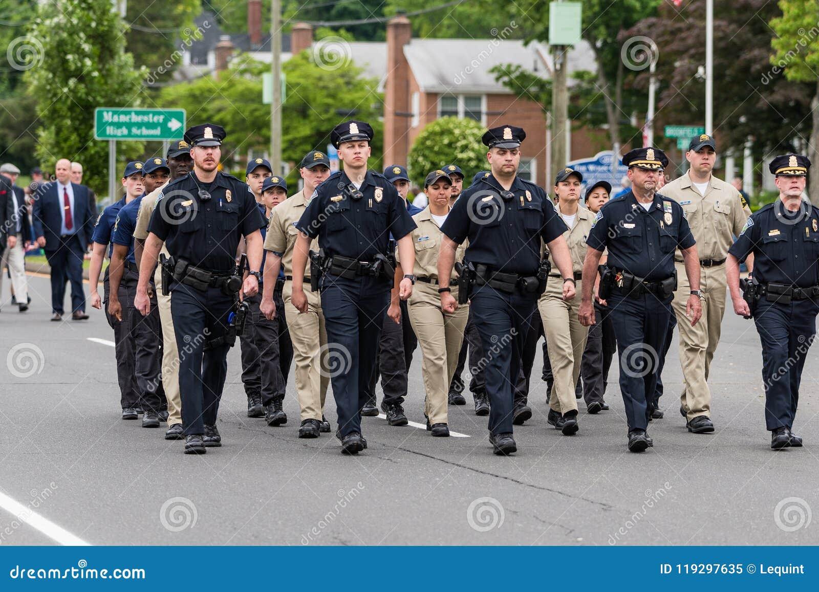 Les policiers et les cadets en uniforme pendant le défilé marchent