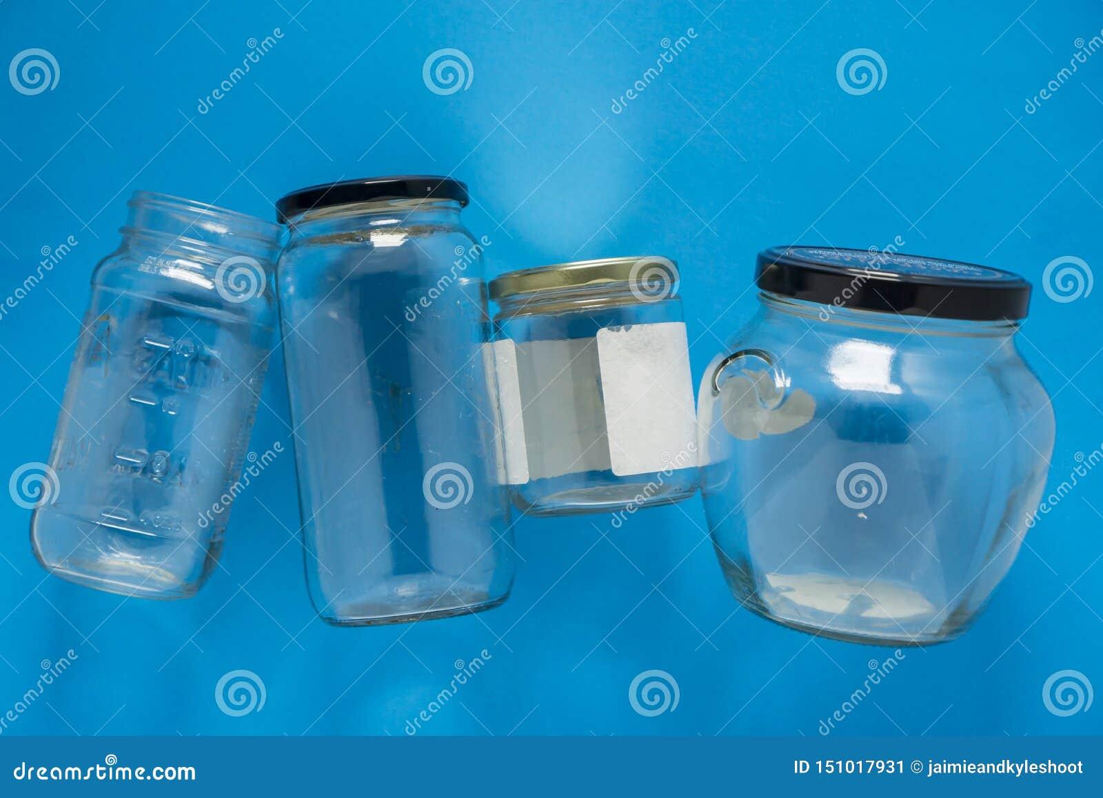 Les pots en verre d isolement se sont étendus à plat et centre sur le fond bleu - réutilisation du programme