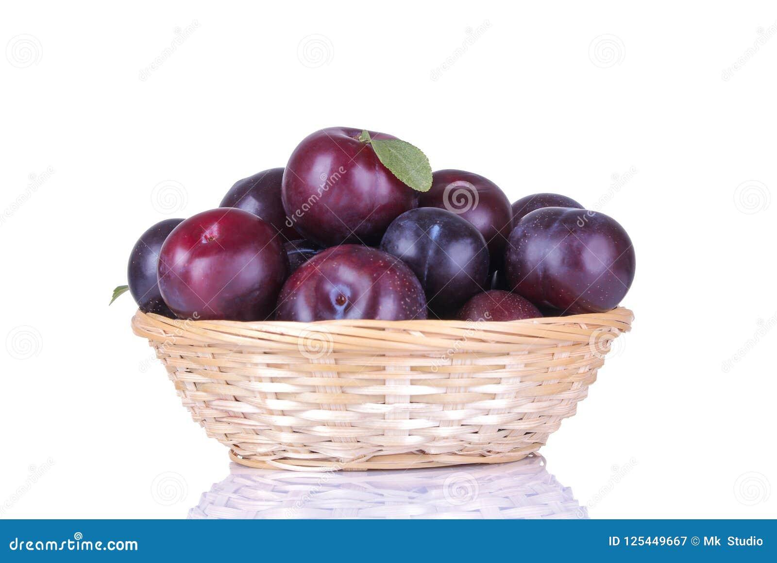Les prunes délicieuses mûres dans un panier en osier sur un blanc ont isolé le fond