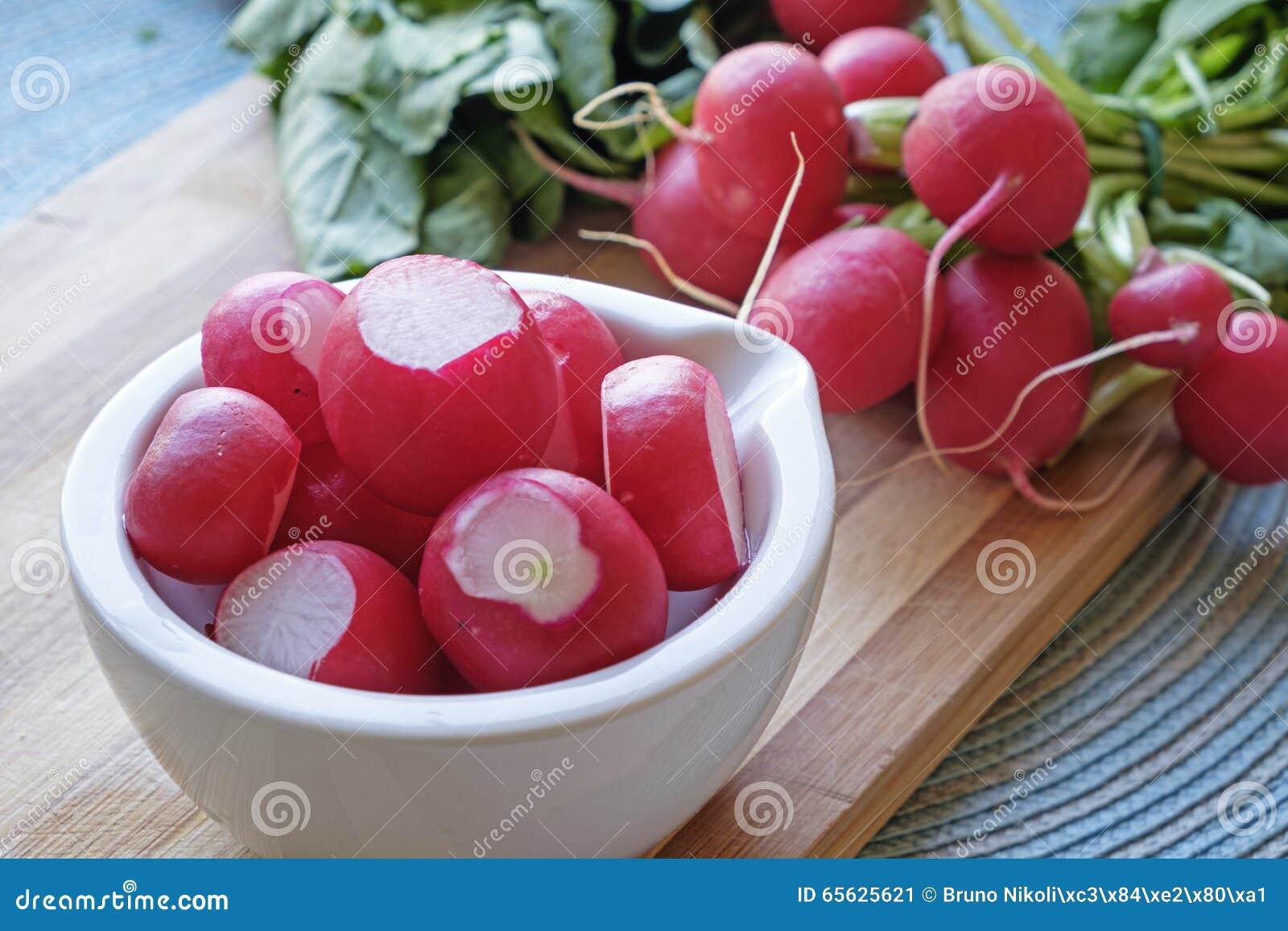 Les radis rouges dans un paysage en céramique blanc de cuvette cultivent