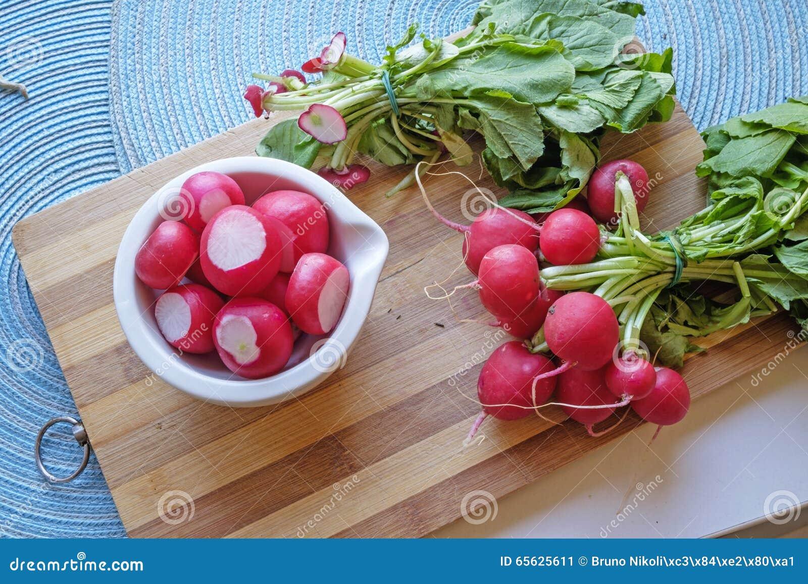 Les radis rouges dans une cuvette en céramique blanche aménagent large en parc supérieur