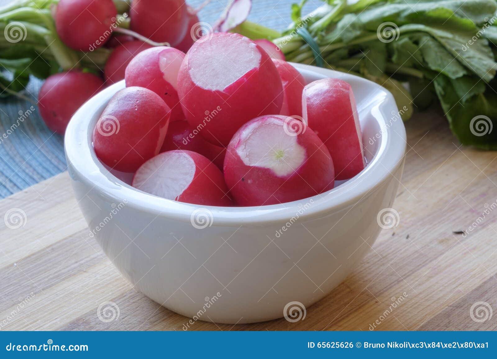 Les radis rouges dans une cuvette en céramique blanche aménagent serré en parc latéral