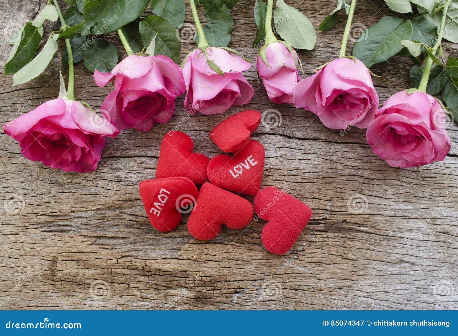 Les roses et le coeur rouge se reposent sur le vieux panneau en bois, le jour de valentines b