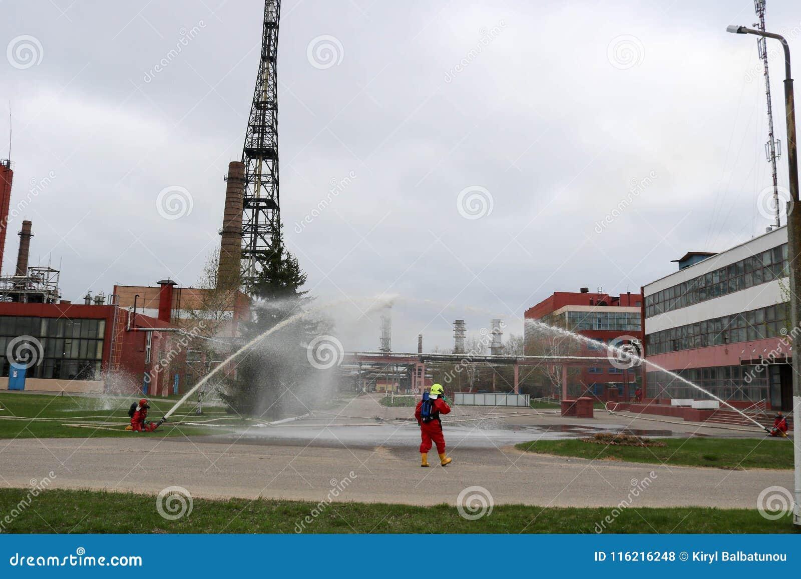 Les sapeurs-pompiers professionnels dans les costumes résistants au feu oranges dans les casques blancs avec des masques de gaz e