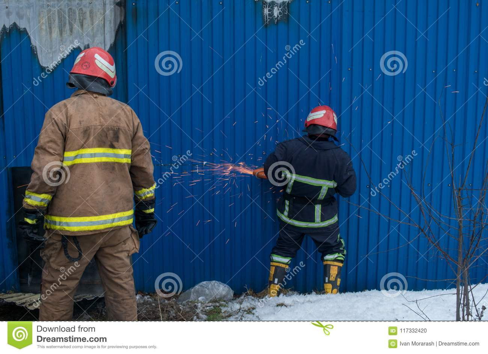 Les sapeurs-pompiers travaillent à un feu du bâtiment utilisant un outil de délivrance de coupeur en métal pendant un feu Le feu