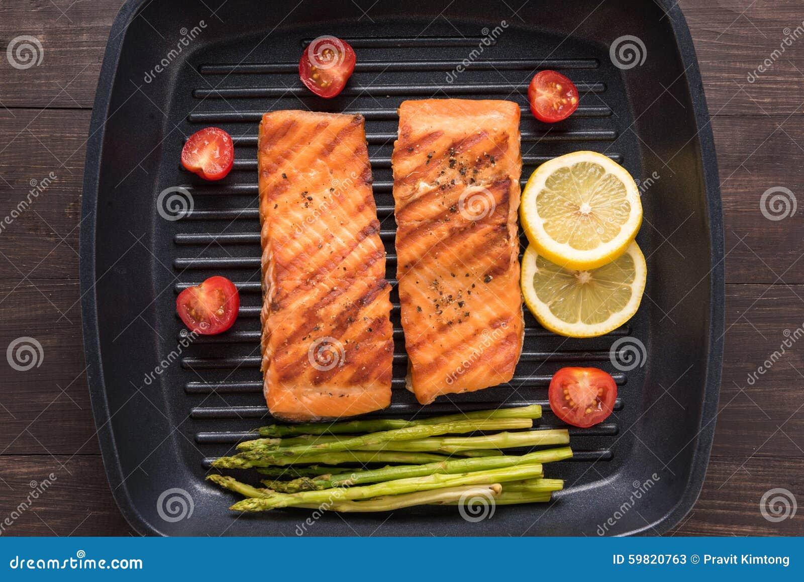 Les saumons grillés ont fait cuire le BBQ sur une casserole sur le fond en bois