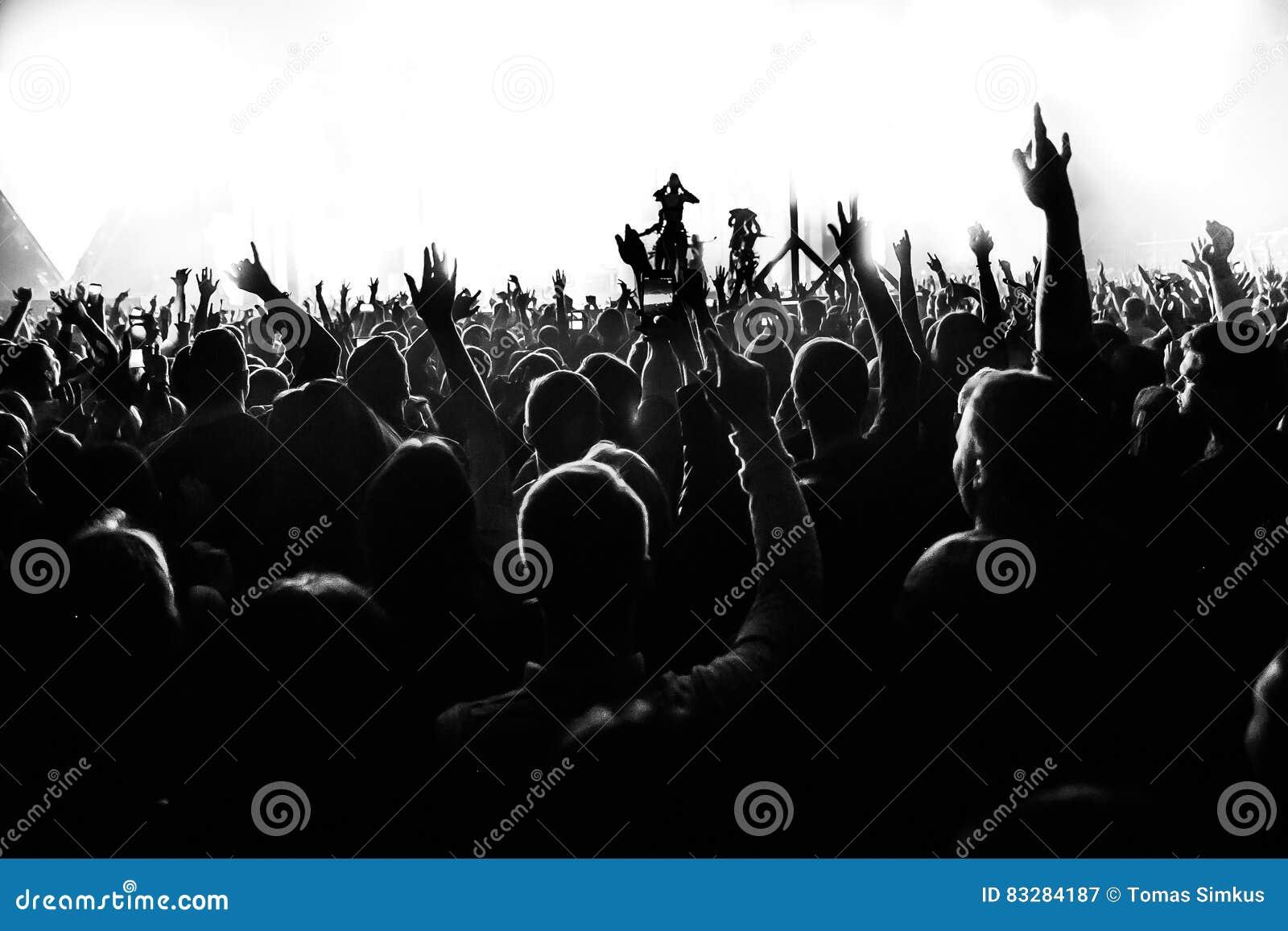 Les silhouettes du concert se serrent devant les lumières lumineuses d étape avec des confettis