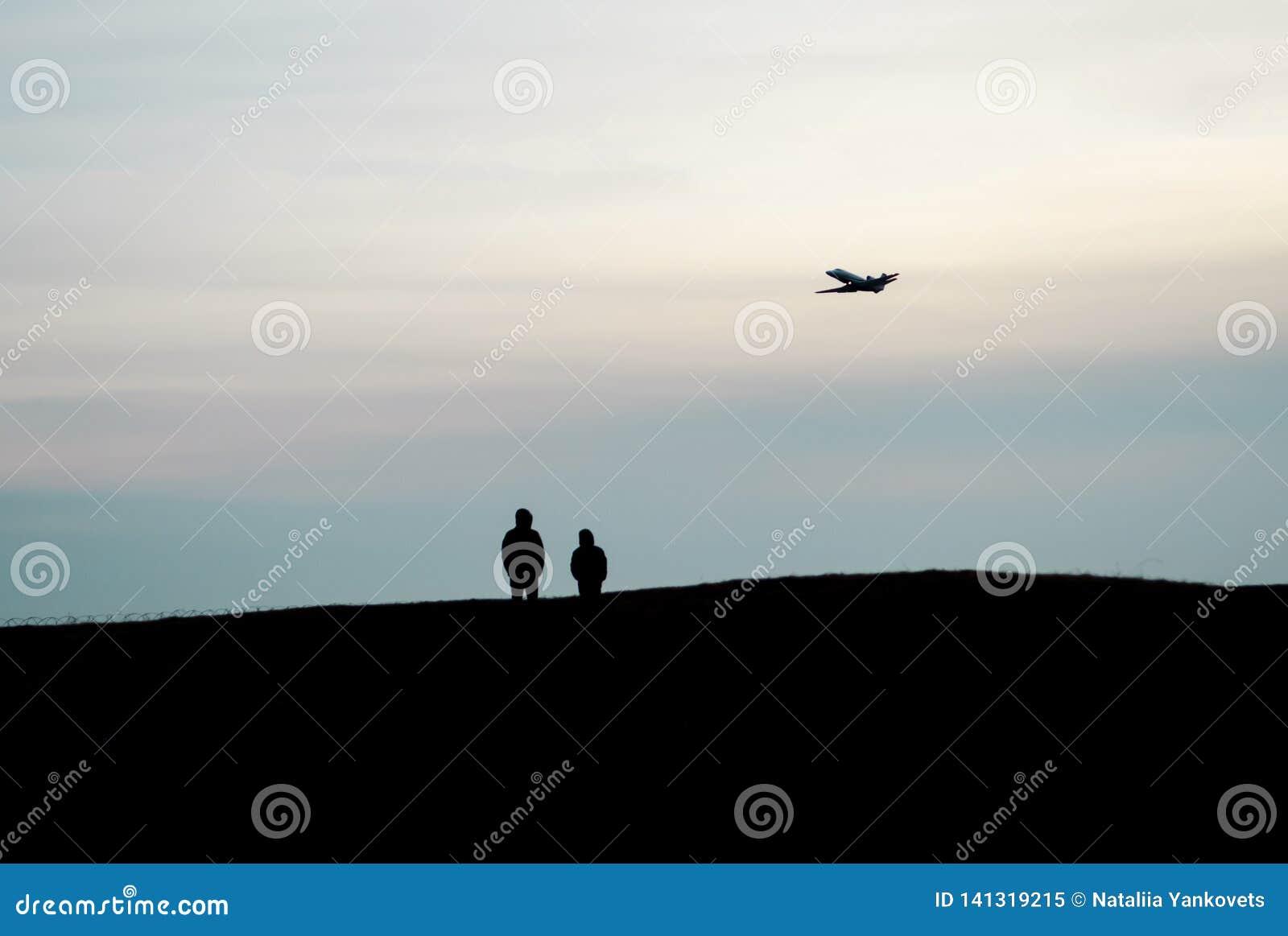 Les silhouettes du support de deux personnes sur une haute colline et observer une haute de vol d avion dans le ciel