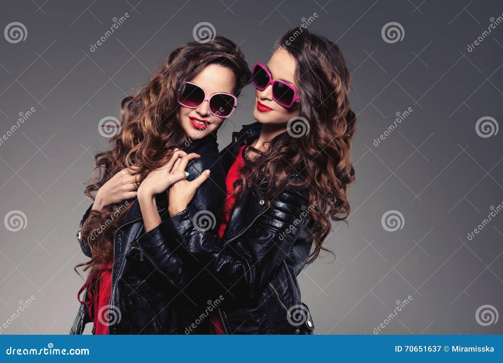 Les soeurs jumelle en verres de soleil de hippie riant deux mannequins