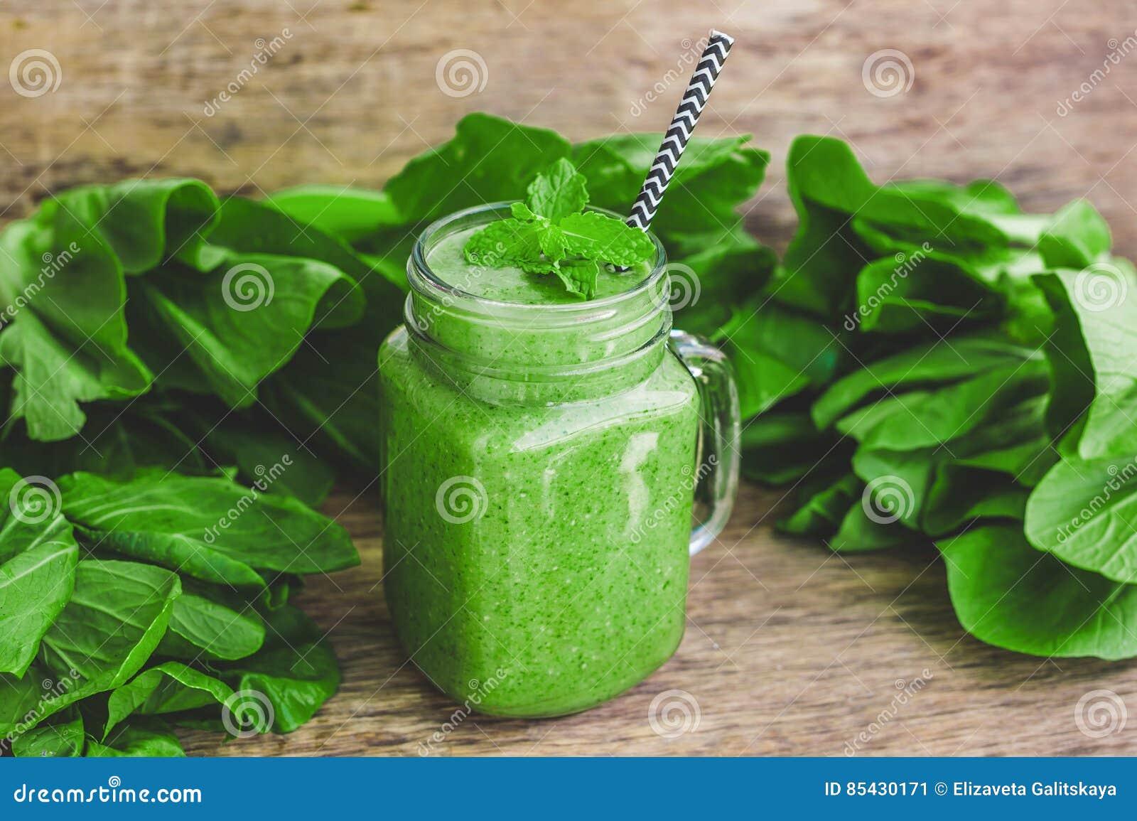 Les tasses de pot de maçon ont rempli de smoothie vert de santé de lait d épinards, de banane et de noix de coco avec avec une cu