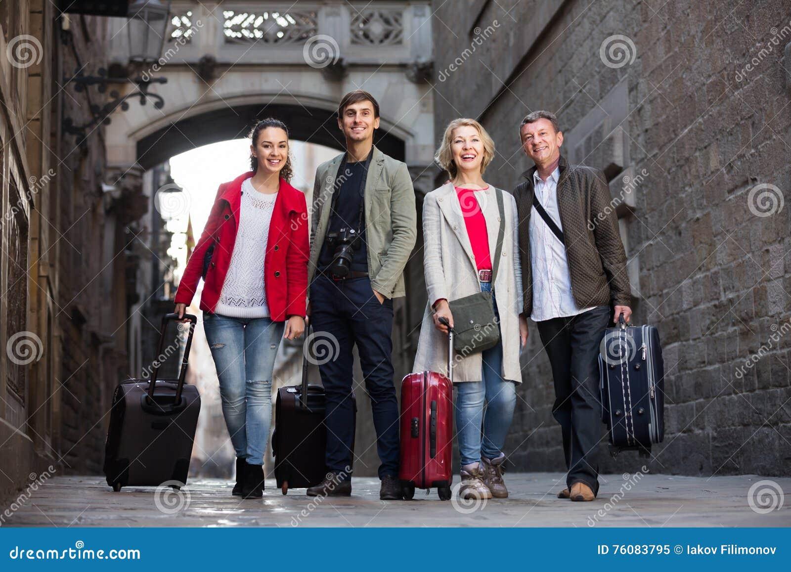 Les touristes avec le bagage posent sur la rue de ville