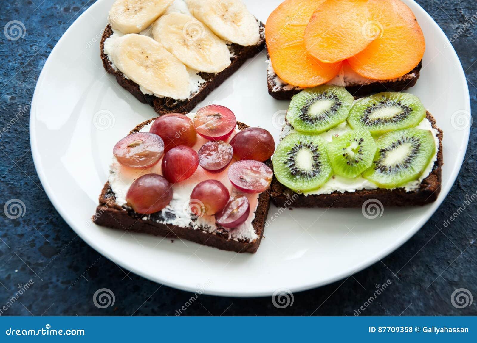 Les tranches de variété de pain de seigle grillent avec des fruits Kaki de banane,