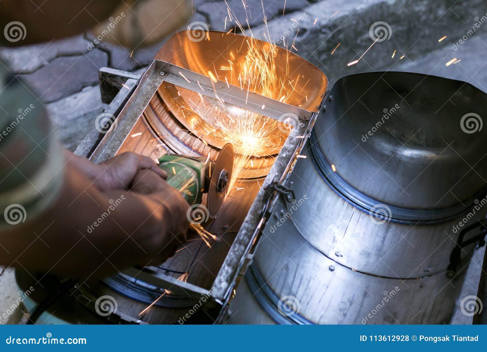 Les travailleurs à l aide des machines de meulage en métal pour couper des objets ont fait o