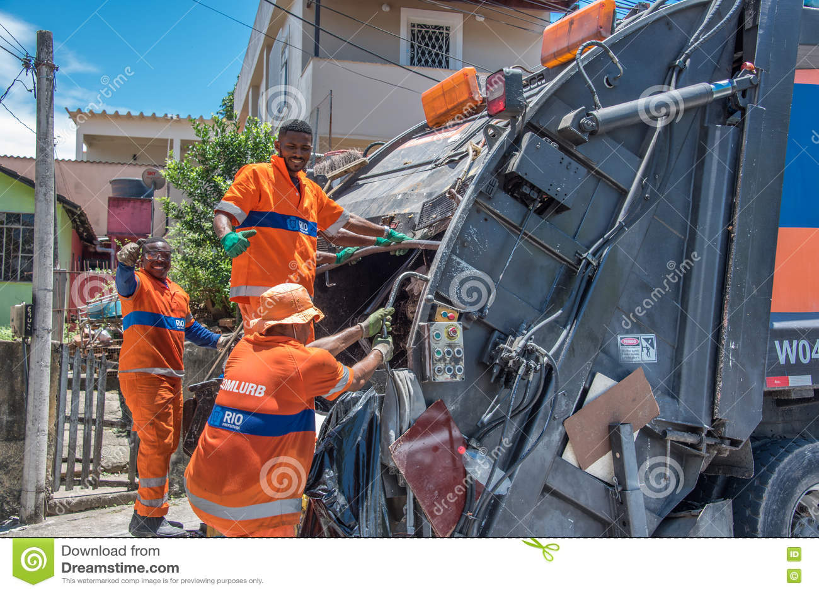 Les travailleurs urbains du COMLURB municipal mettant des déchets dans réutiliser le camion à ordures