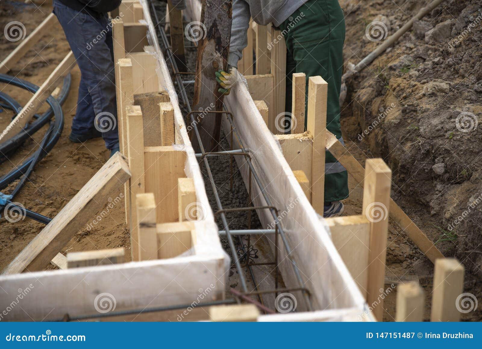 Les travailleurs versent concret dans la base