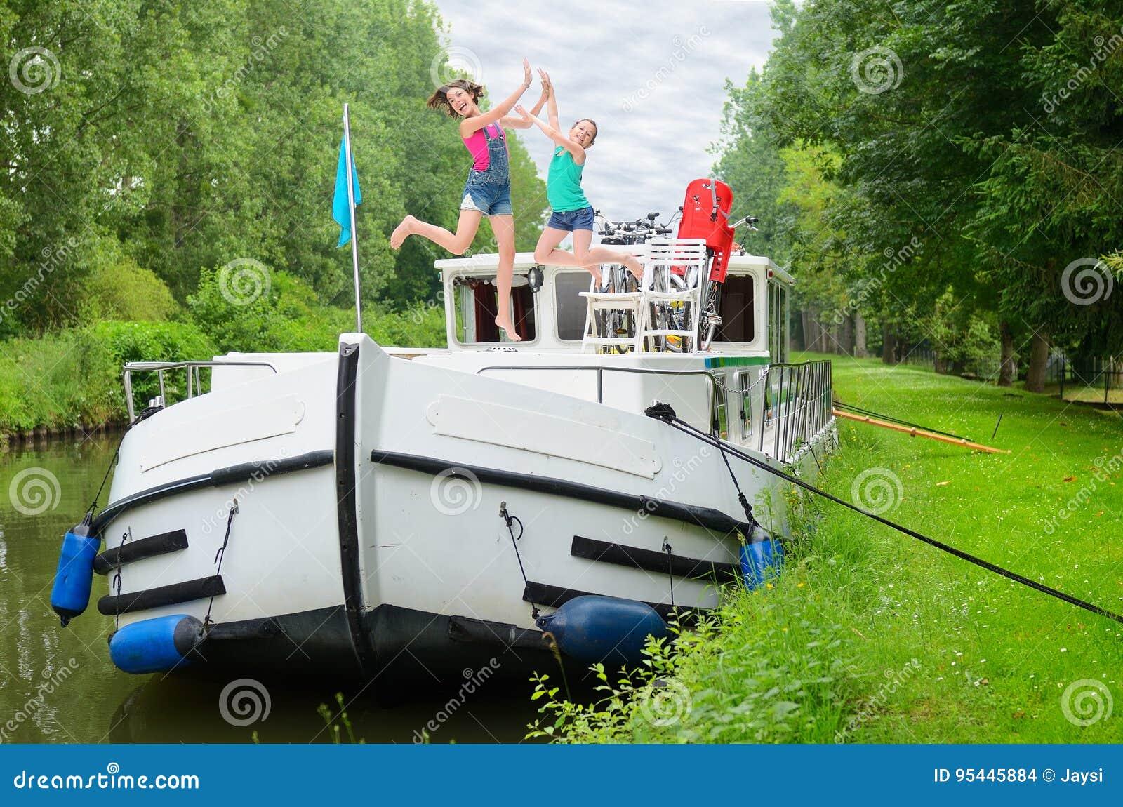 Les vacances de famille, voyage sur le bateau de péniche dans le canal, les parents heureux avec des enfants sur la croisière de