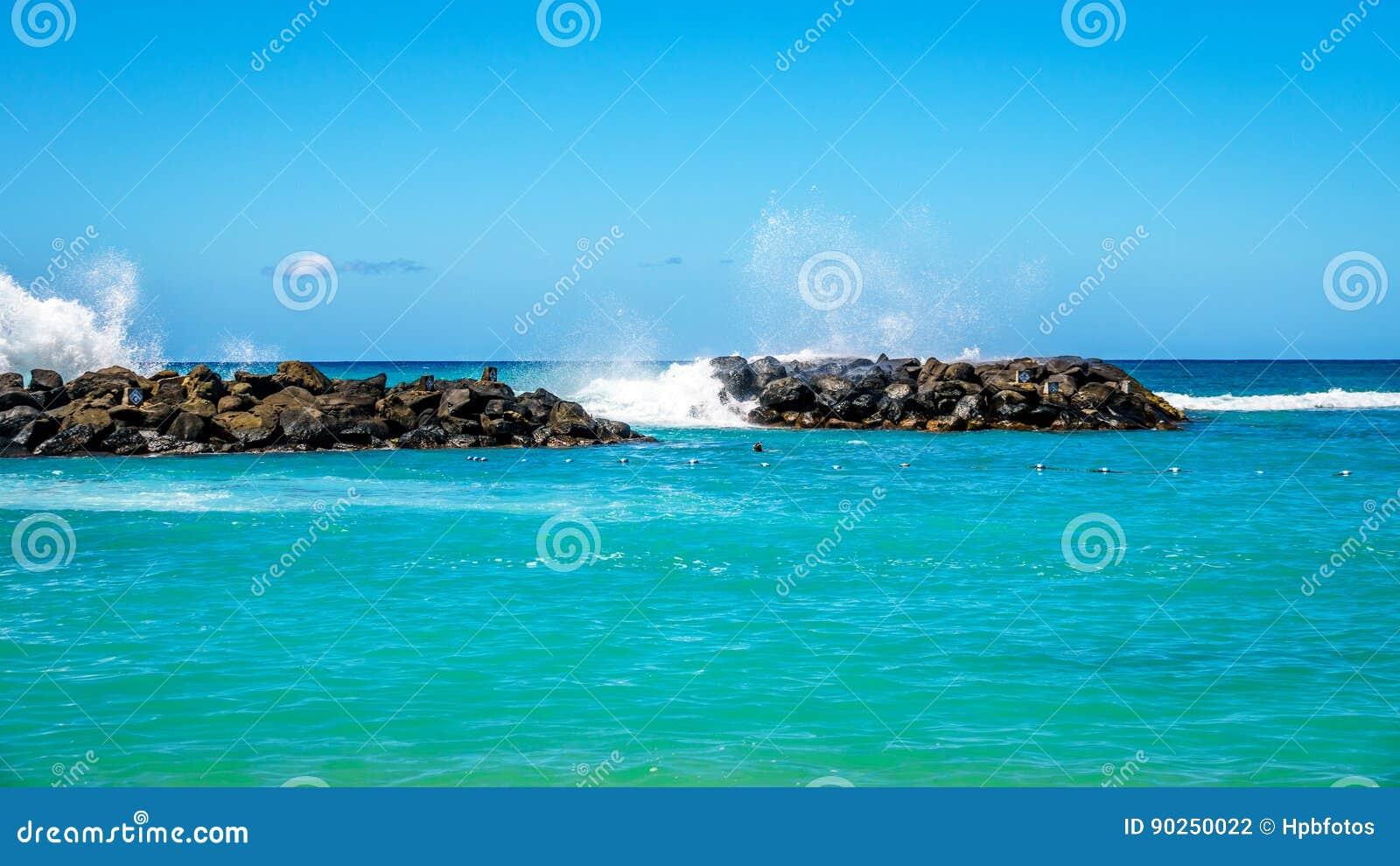 Les vagues de l océan pacifique se brisant sur les roches des barrières à l homme ont fait des lagunes sur le rivage de Ko Olina