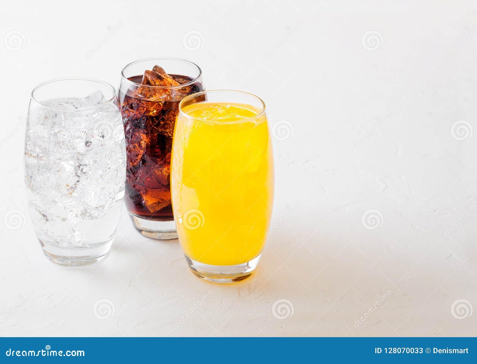 Les verres de soude boivent avec des glaçons et des bulles sur le fond en pierre de table de cuisine Kola et soude orange de limo