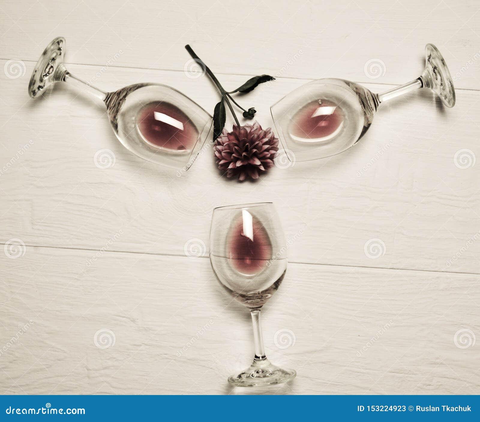 Les verres transparents se trouvent avec le vin rouge sur un fond blanc