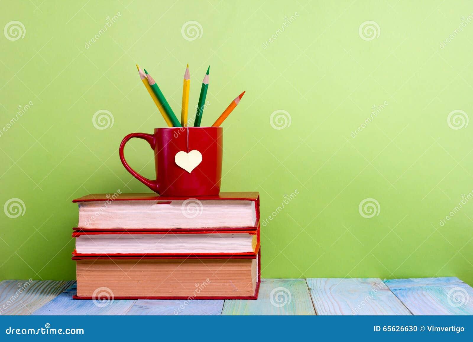 Les vieux livres et tasse de vintage avec le coeur forment sur la table en bois