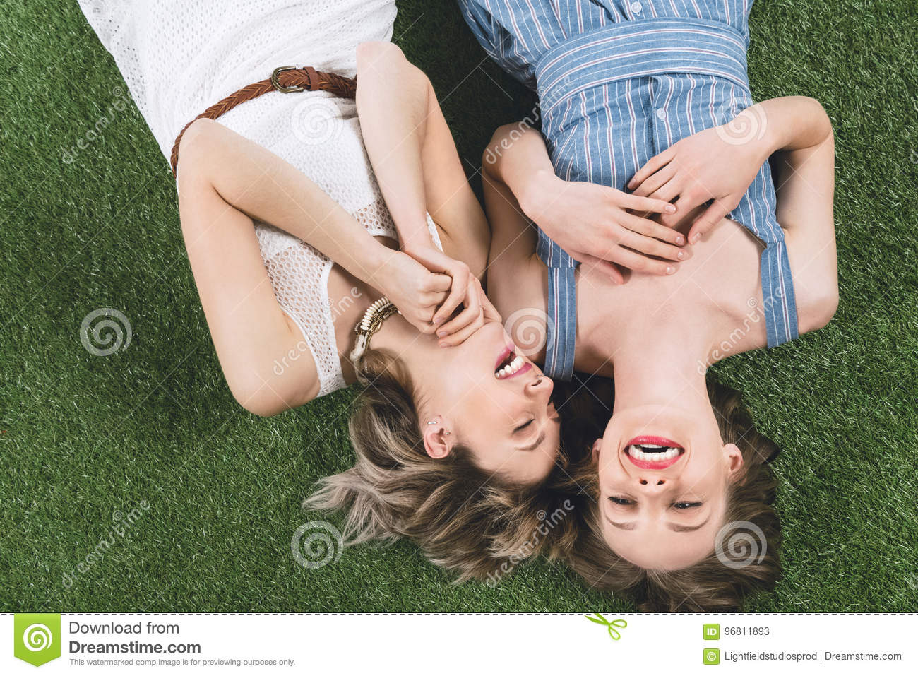 Lesbian couple laughing while lying together on the grass