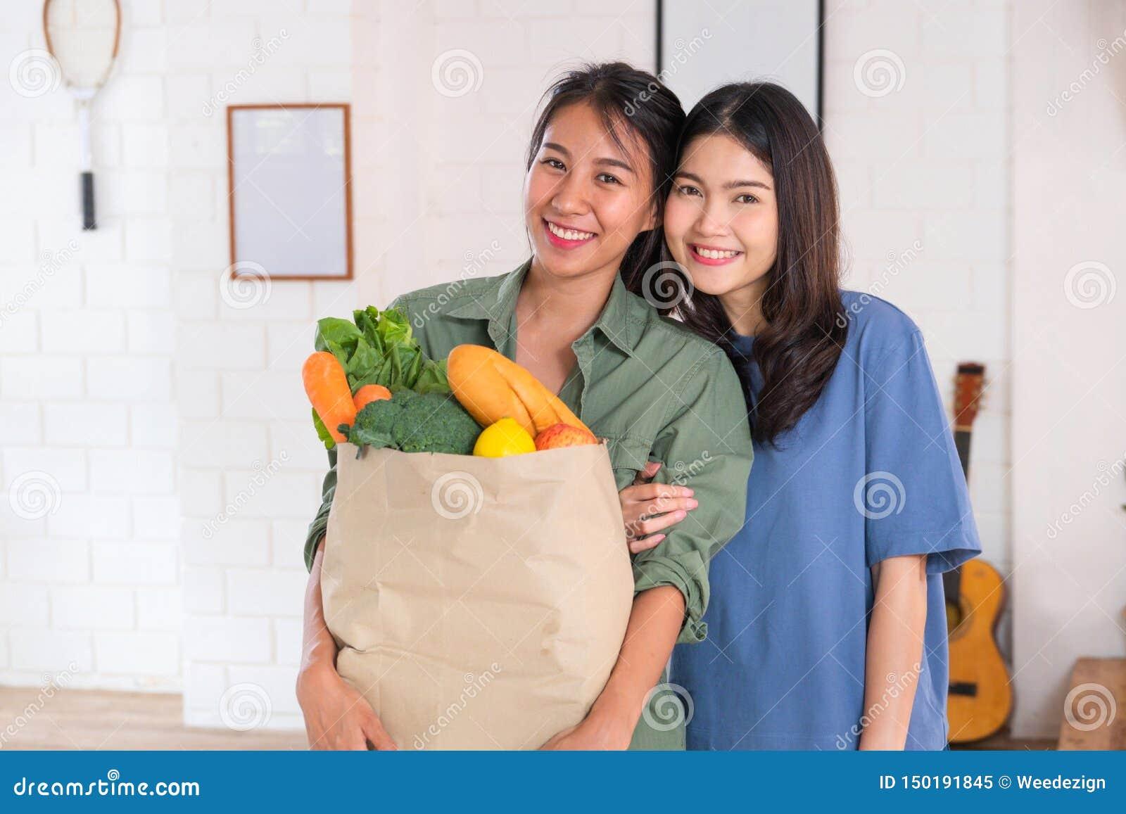 Lesbica asiatica felice delle coppie che tiene borsa di verdure che looing alla macchina fotografica dopo la compera alla drogher