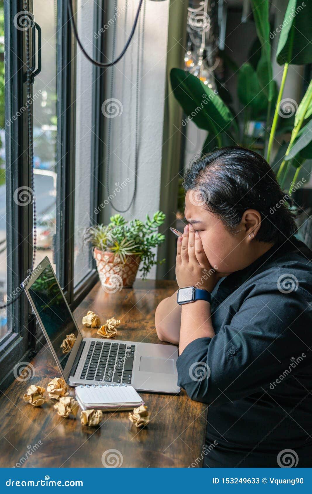 Lesbica asiatica frustrata che si siede con il computer portatile e le palle di carta sgualcite