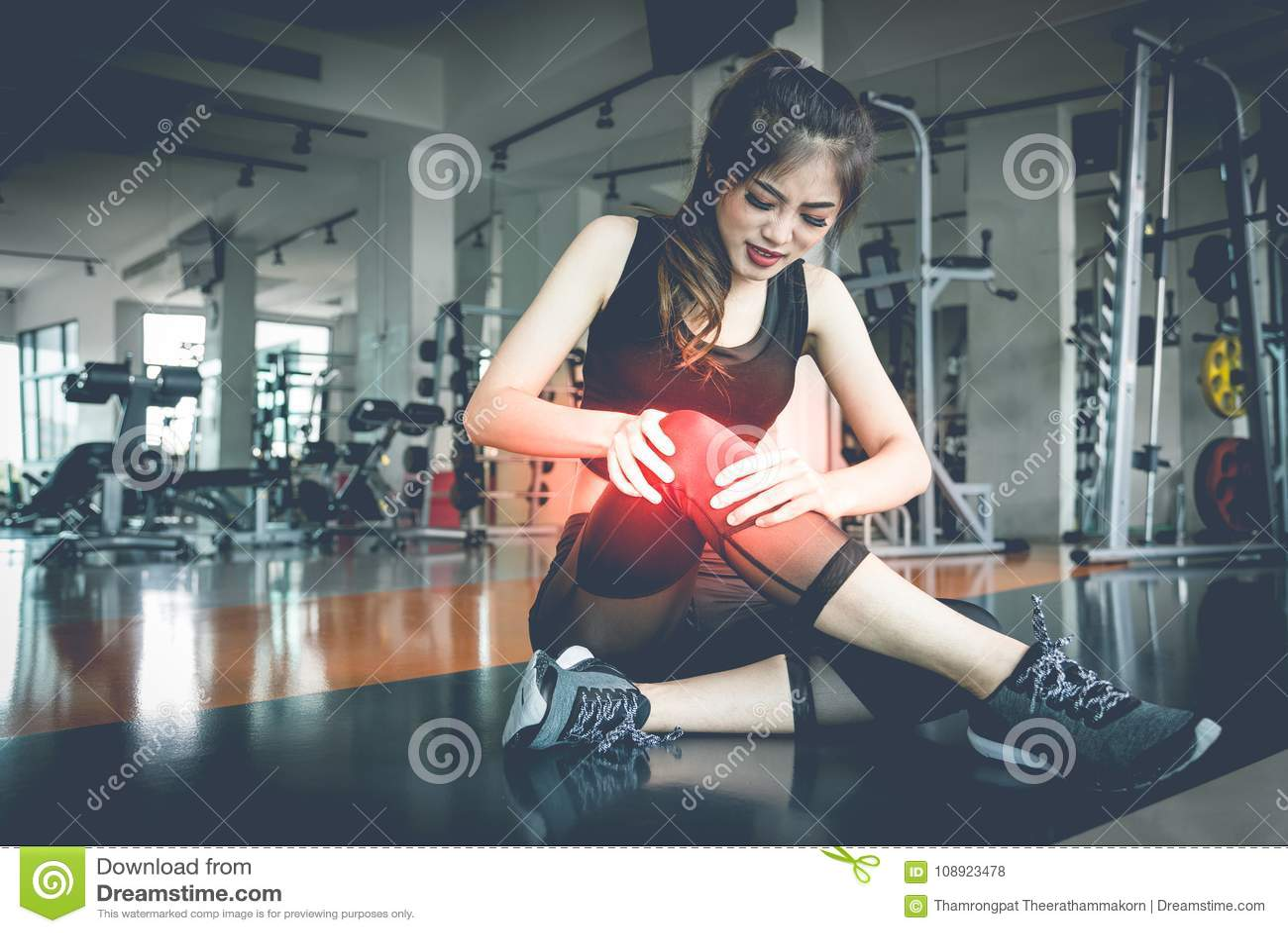 Lesiones asiáticas de la mujer durante entrenamiento en la rodilla en gimnasio de la aptitud Medi