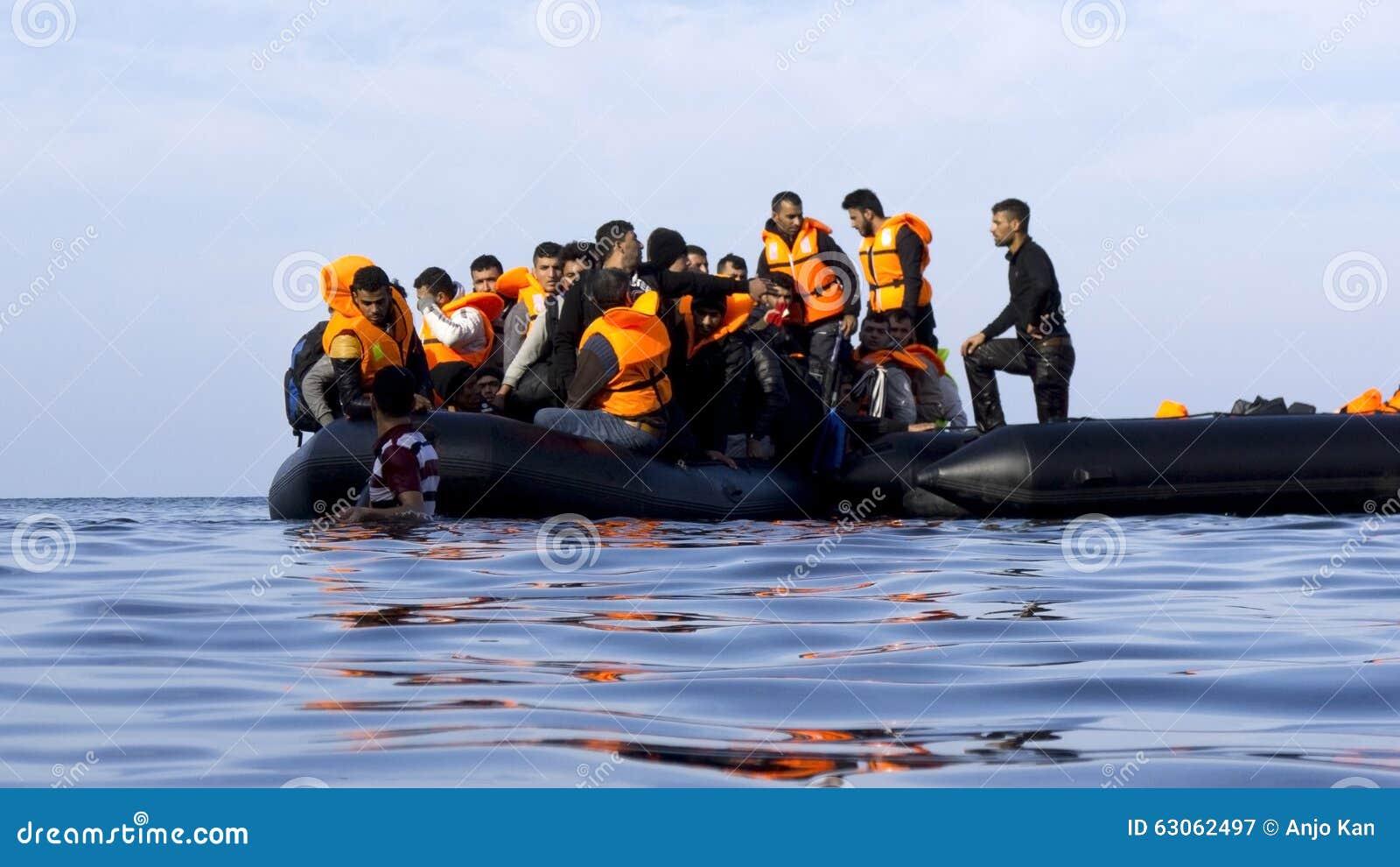 LESVOS, ГРЕЦИЯ 18-ое октября 2015: Беженцы приезжая в Грецию в тусклой шлюпке от Турции