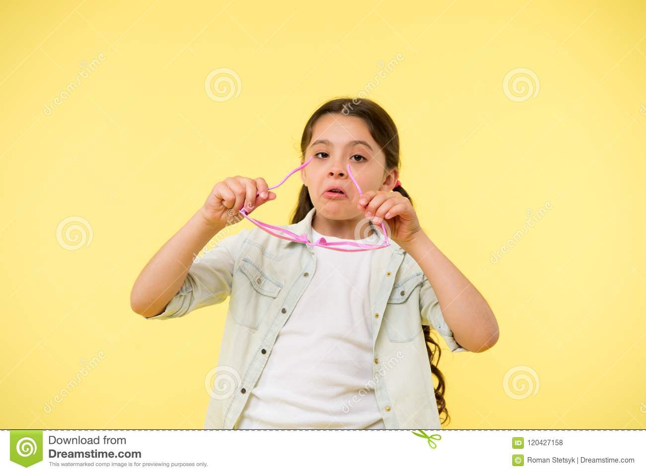 Let me see. Kid girl puts heart shaped eyeglasses. Girl serious face putting glasses on. Child serious holds eyeglasses
