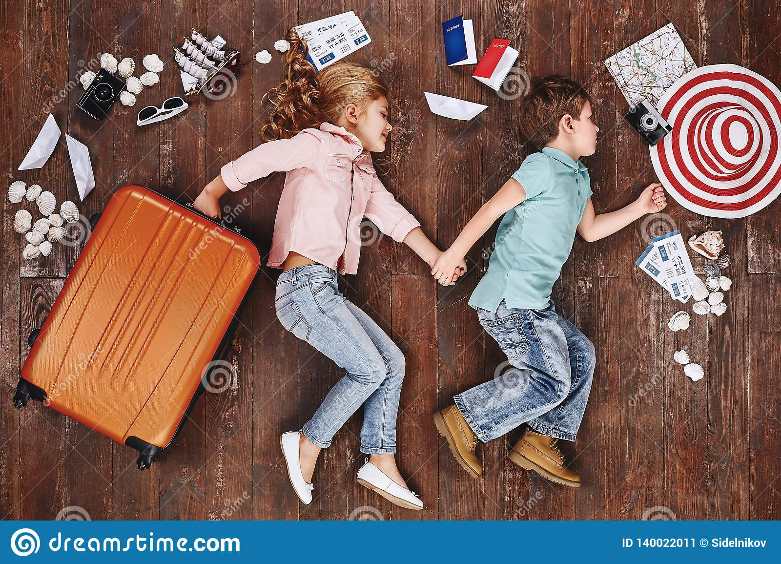 Let`s be adventurers. Children lying near travel items. Girl with suitcase