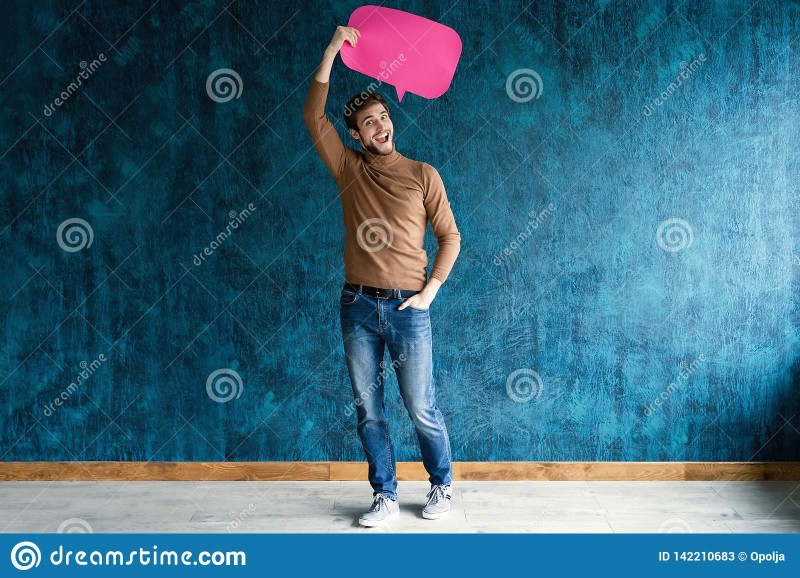 Let`s start a conversation. I speak the language of success. Handsome young man holding up speech bubble  on