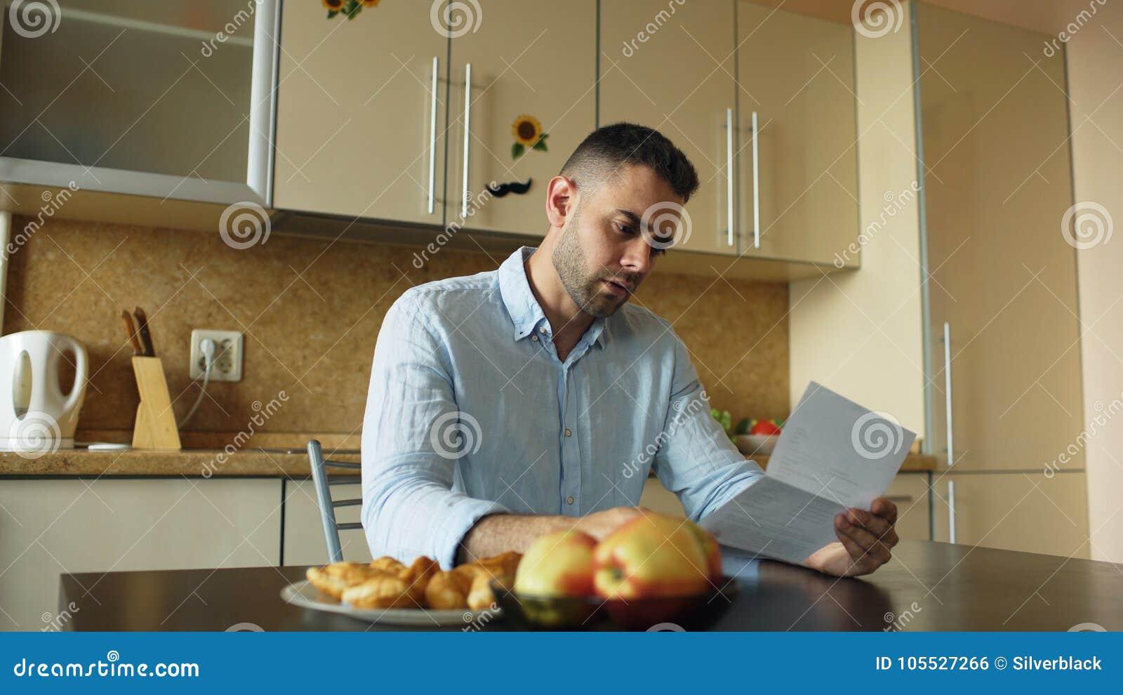 Letra virada da leitura do homem novo com conta por pagar na cozinha em casa
