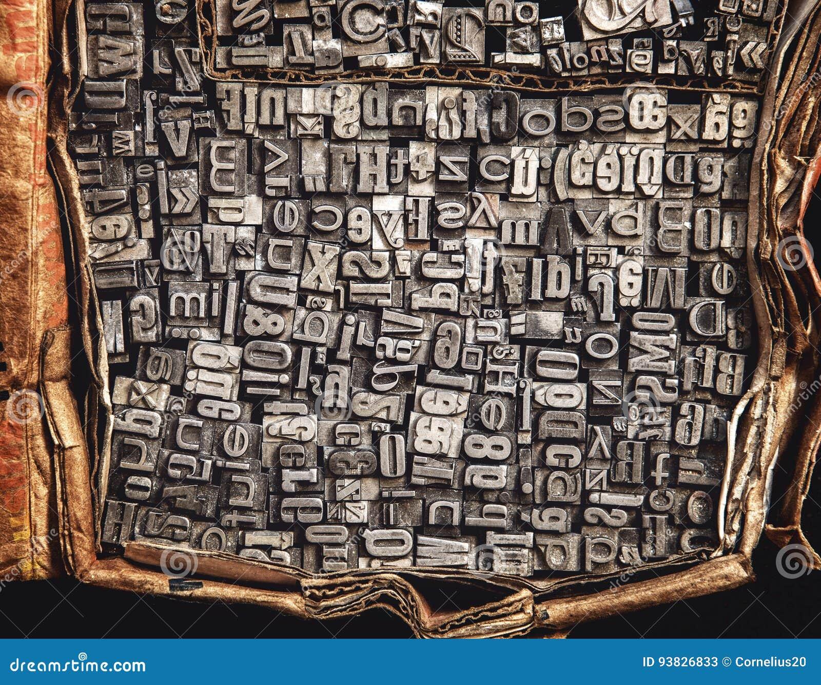 Letras del metal en una caja de cartón