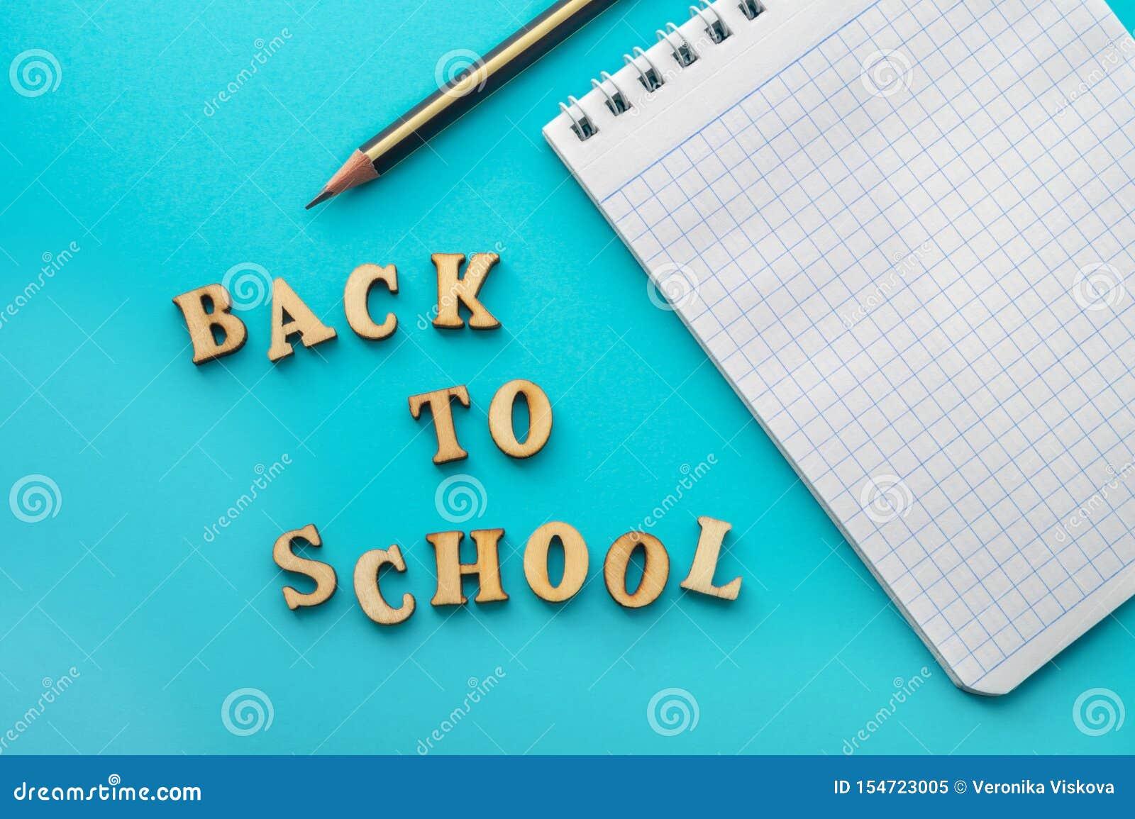 Letras, lápiz y cuaderno en fondo de la turquesa Desde arriba de la inscripción de nuevo a escuela y del lápiz con el cuaderno en
