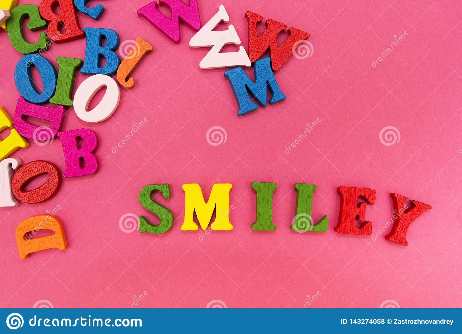 Letras multicoloras dispersadas en un fondo rosado, la palabra