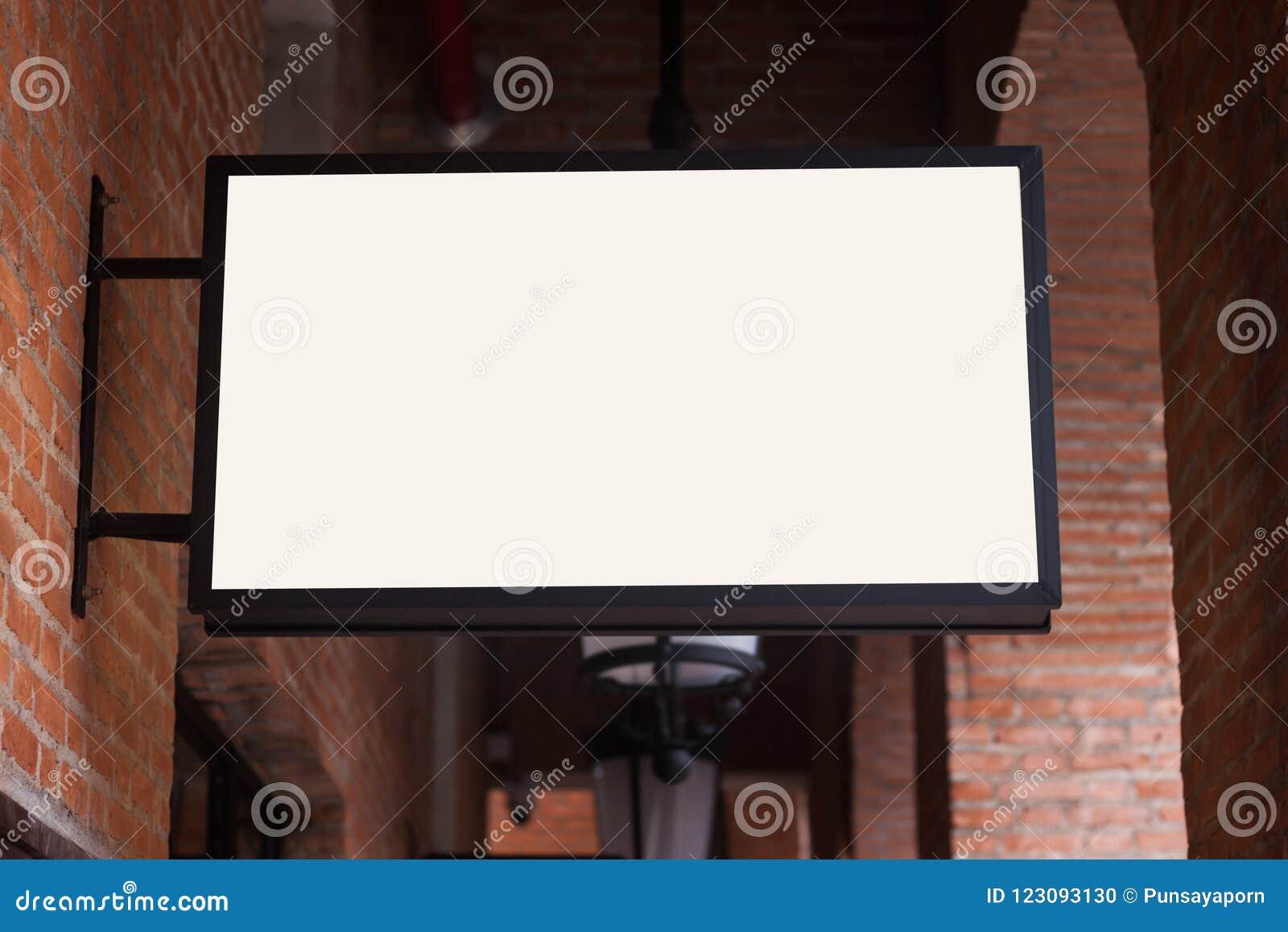 Letrero blanco del regtangle en la pared de ladrillo
