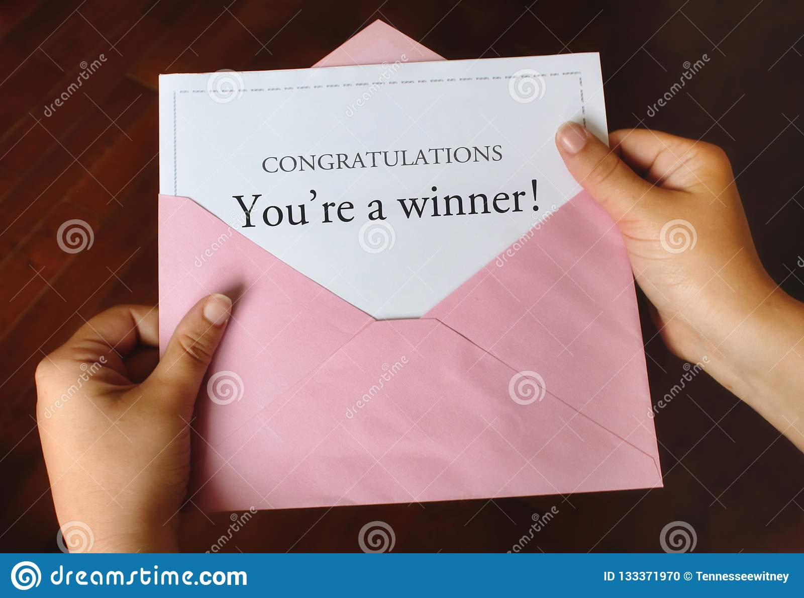 A letter that says Congratulations You`re a winner! with hands holding a pink envelope