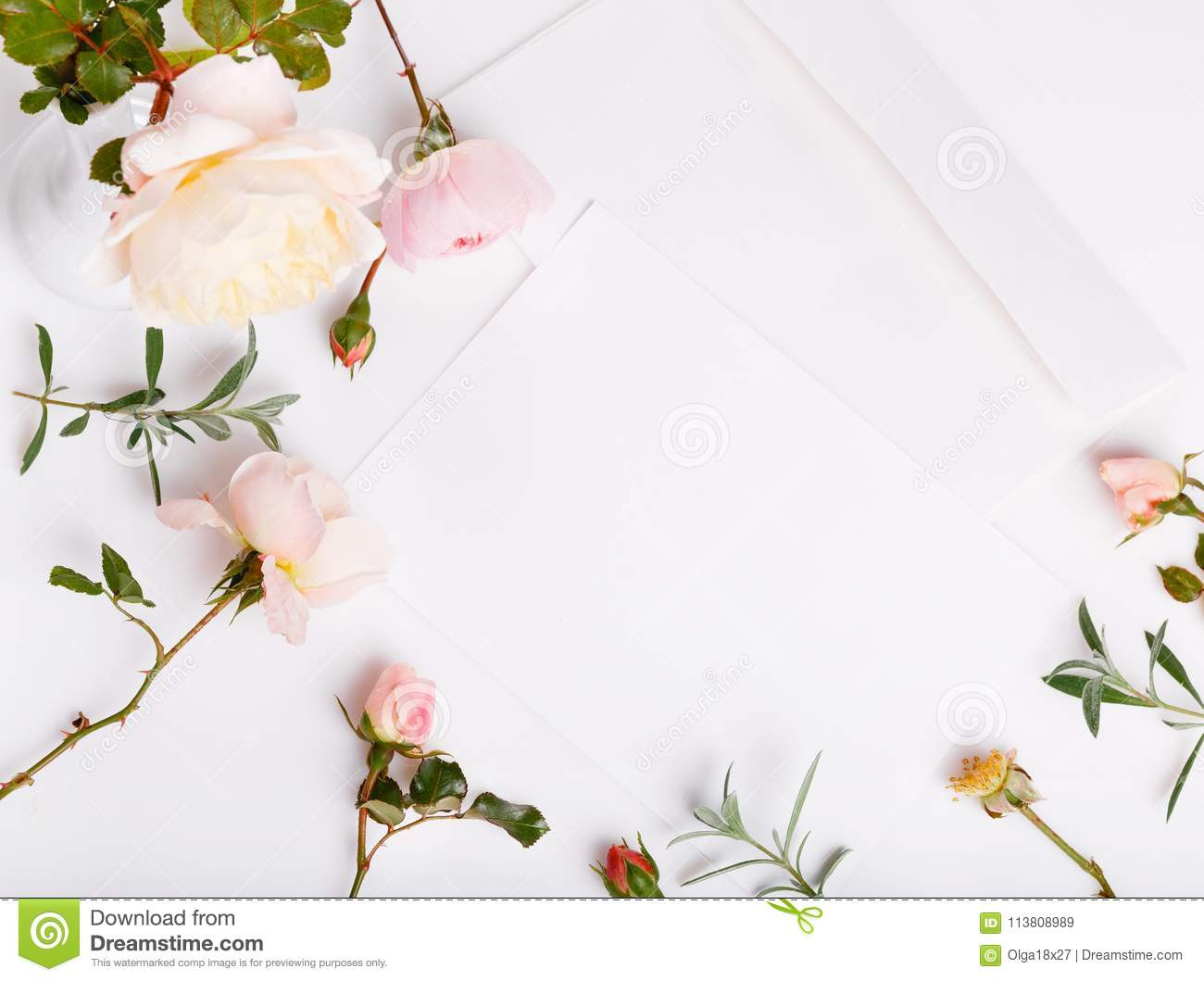 letter pen and white envelope on white background with pink english rose invitation cards